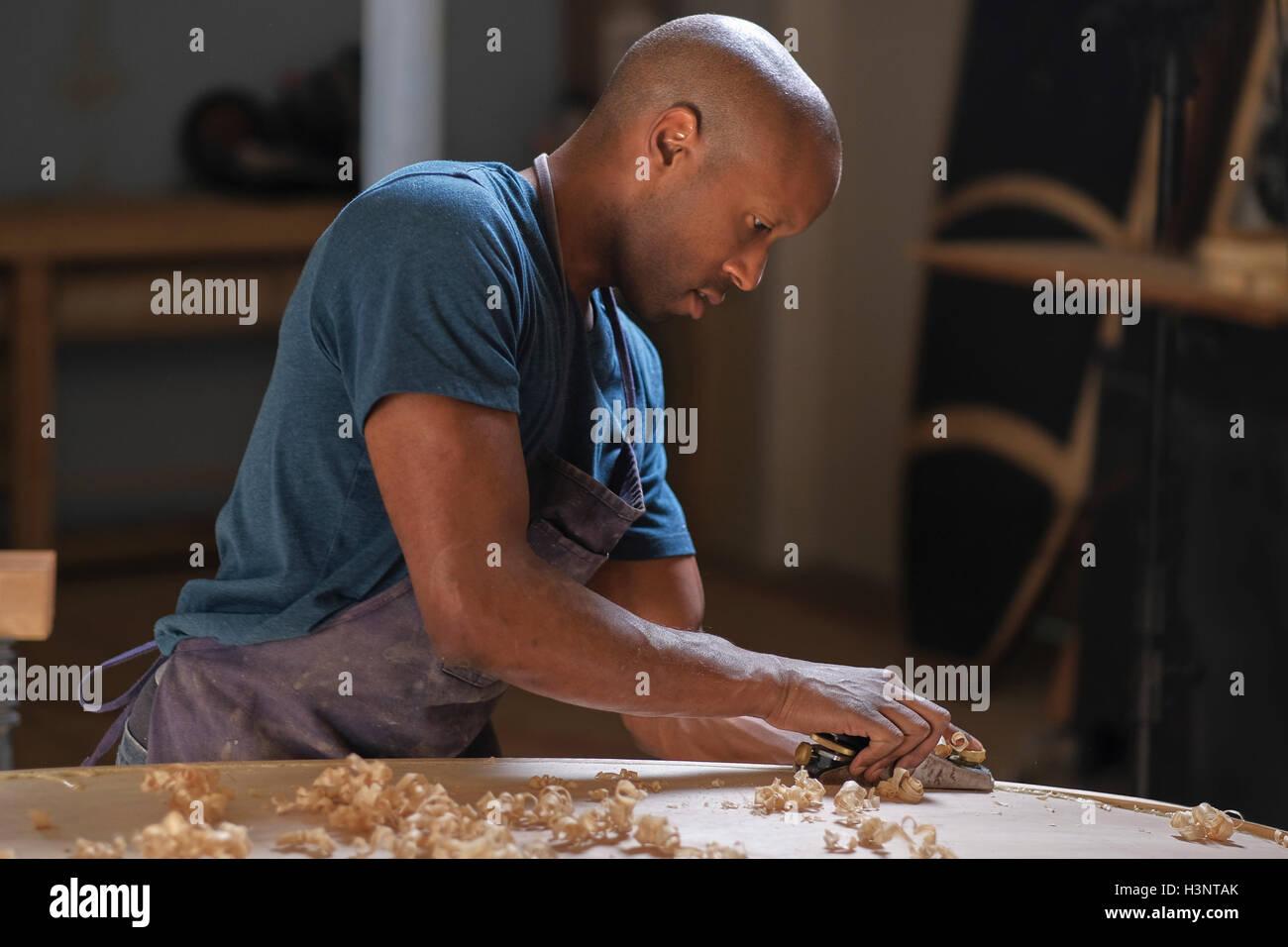 Craftsman making paddleboard in workshop - Stock Image