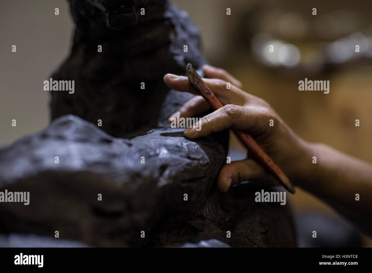 Cropped view of sculptor in artists' studio creating sculpture with hand tool - Stock Image