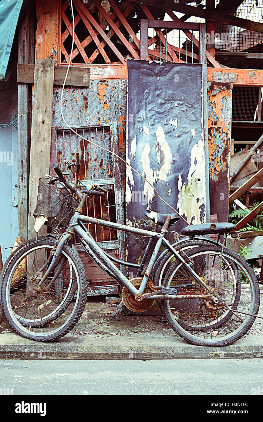Old abandoned bicycles outside an old house in Tai O fishing village, Lantau island, Hong Kong S.A.R. - Stock Image