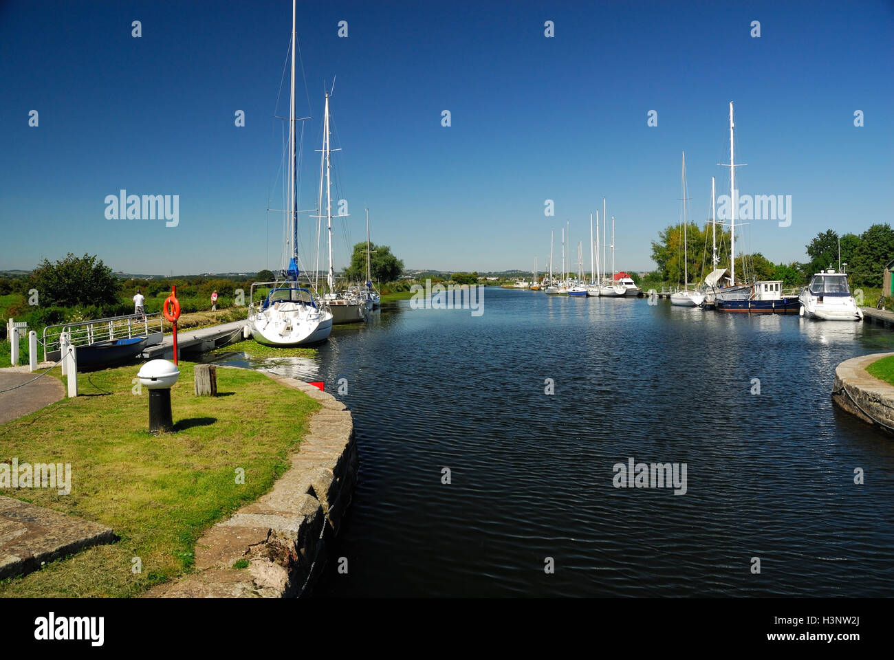 Boats moored alongside the Exeter canal near Turf Lock. - Stock Image