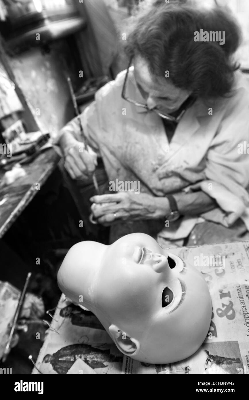 The old lady artisan Gelsy repair a doll's head in the restoration shop called 'Doll Hospital' in Via - Stock Image
