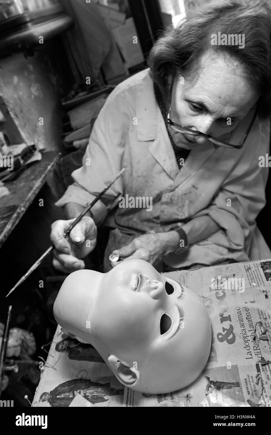 The old lady artisan Gelsy repairs a doll's head in the restoration shop called 'Doll Hospital' in Via - Stock Image