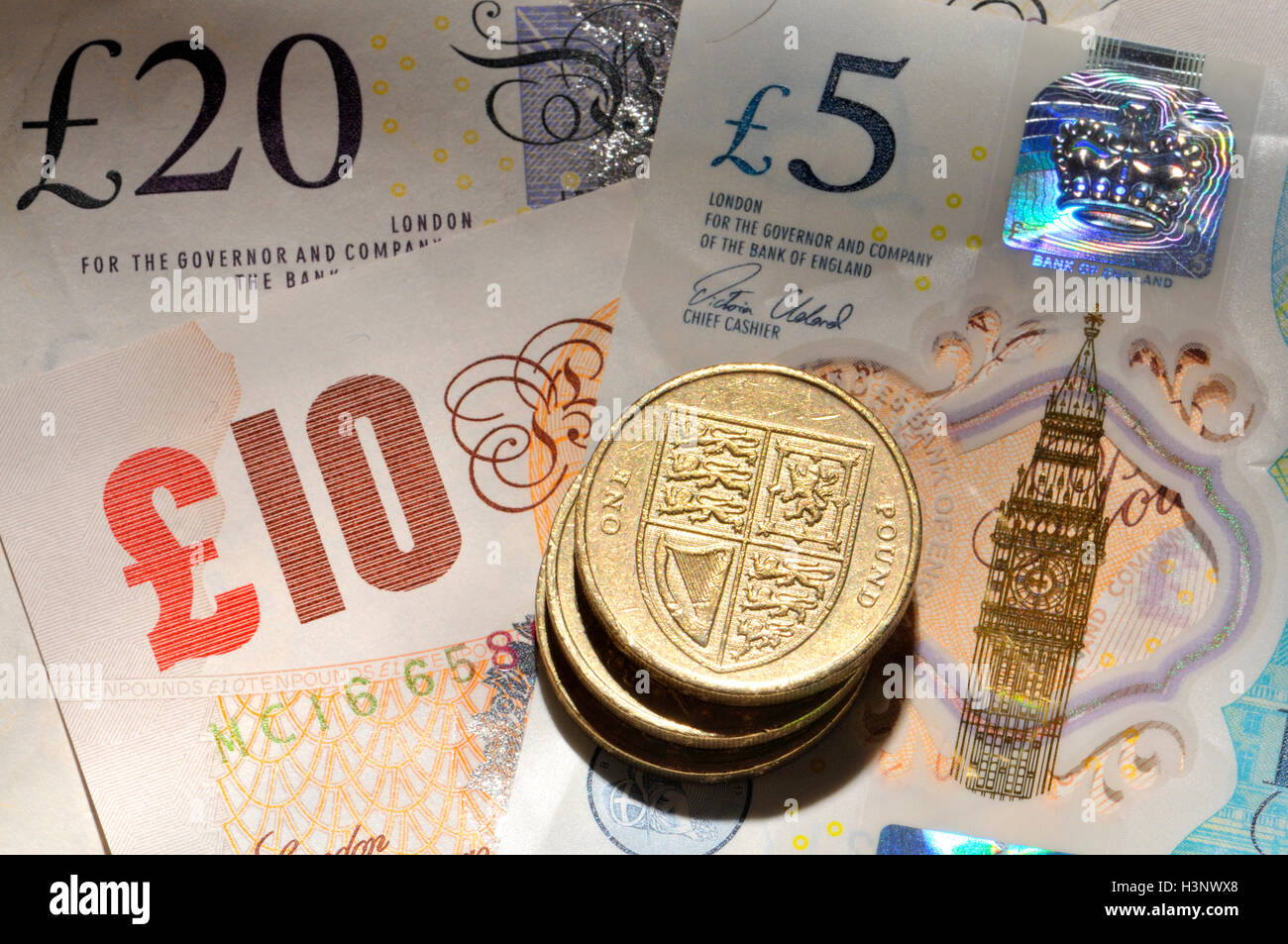 British money - pound coins on notes, including new (2016) plastic £5 - Stock Image