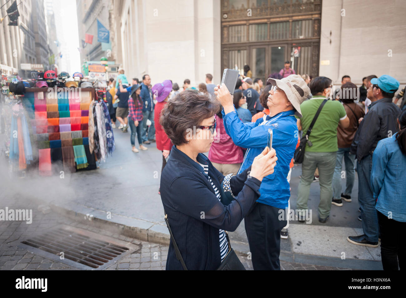 Asian tourists on Wall Street in New York on Friday, October 7, 2016 take photographs with their smartphones. (© - Stock Image