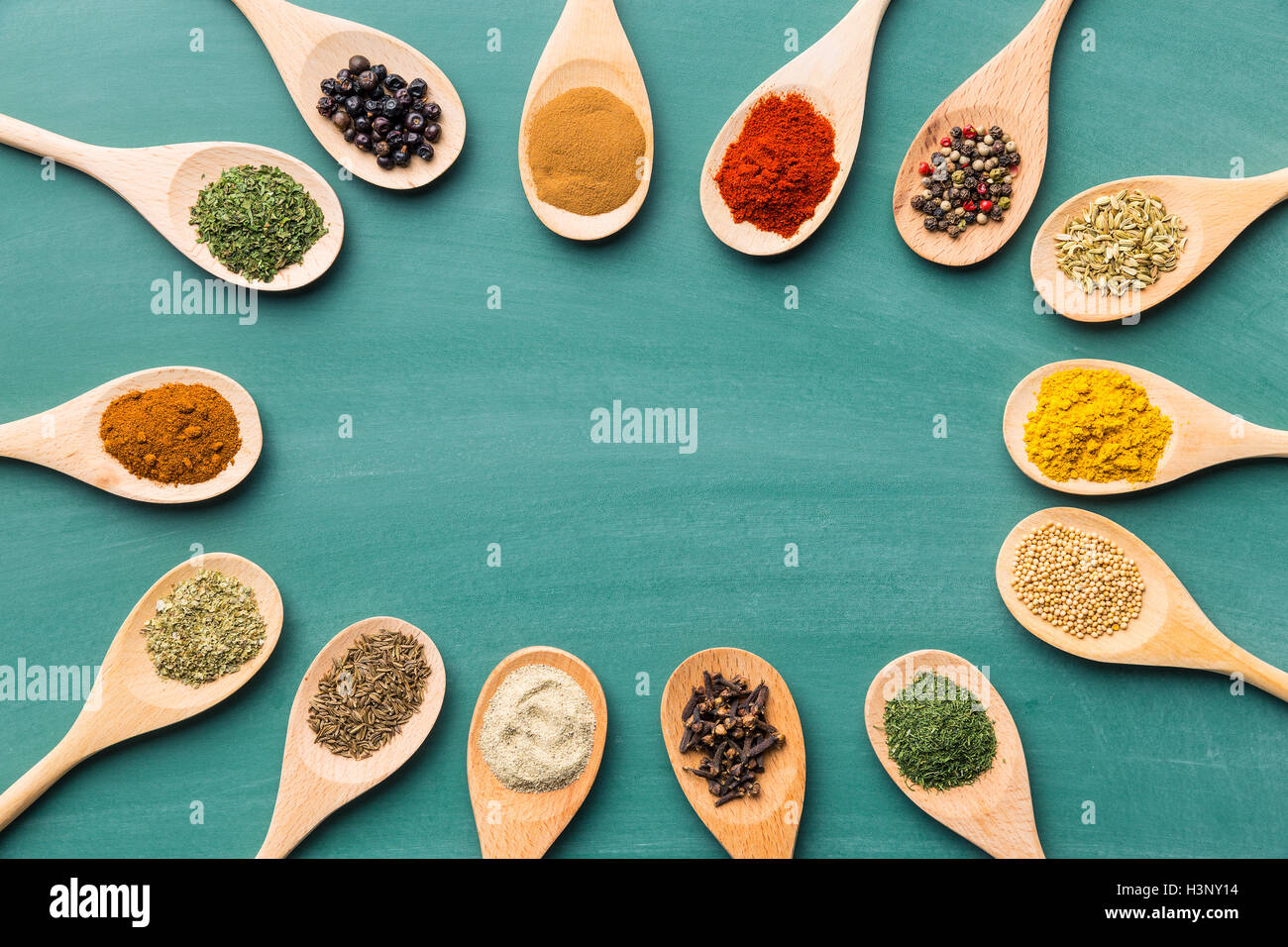 Various spices in wooden spoons on chalkboard. Top view Stock Photo ...