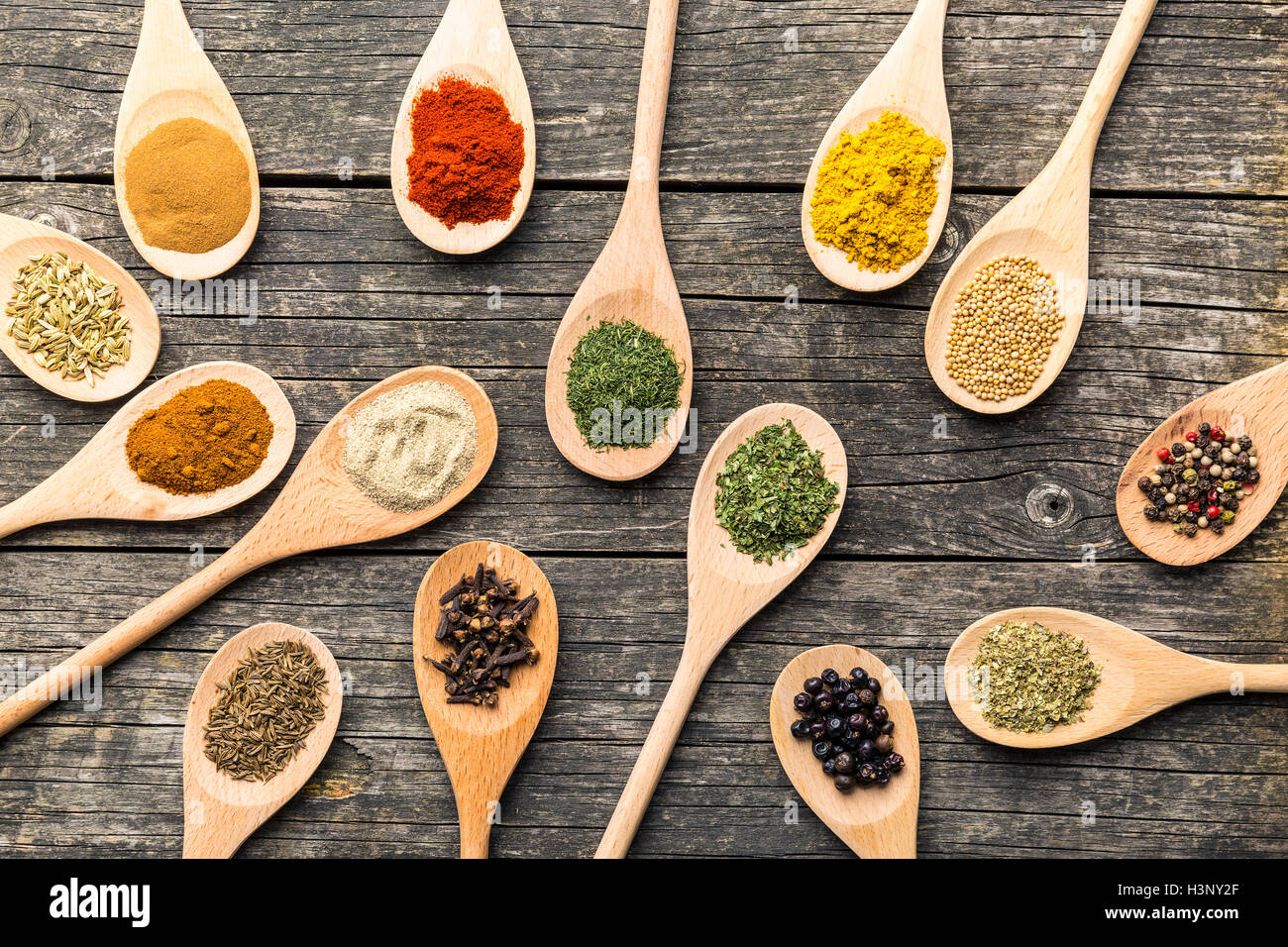 Various spices in wooden spoons on old wooden table. Top view. - Stock Image