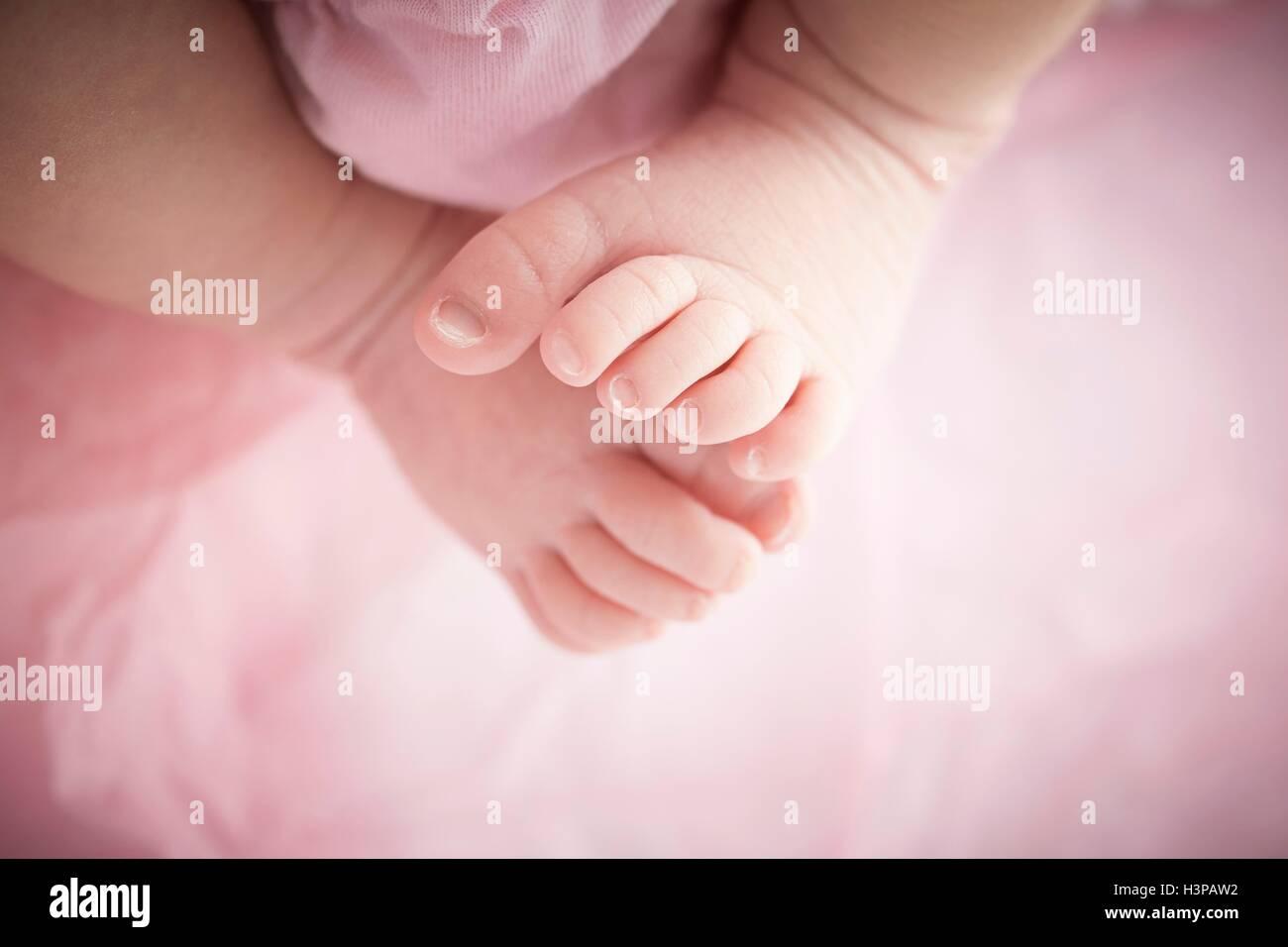 MODEL RELEASED. Newborn baby girl's bare feet, close up. - Stock Image