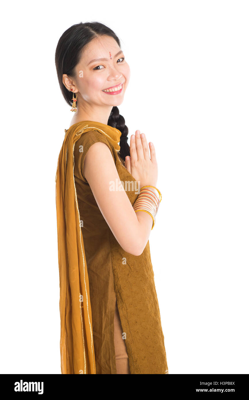 2257bf1070 Portrait of young mixed race Indian Chinese female in traditional punjabi  dress greeting, standing isolated