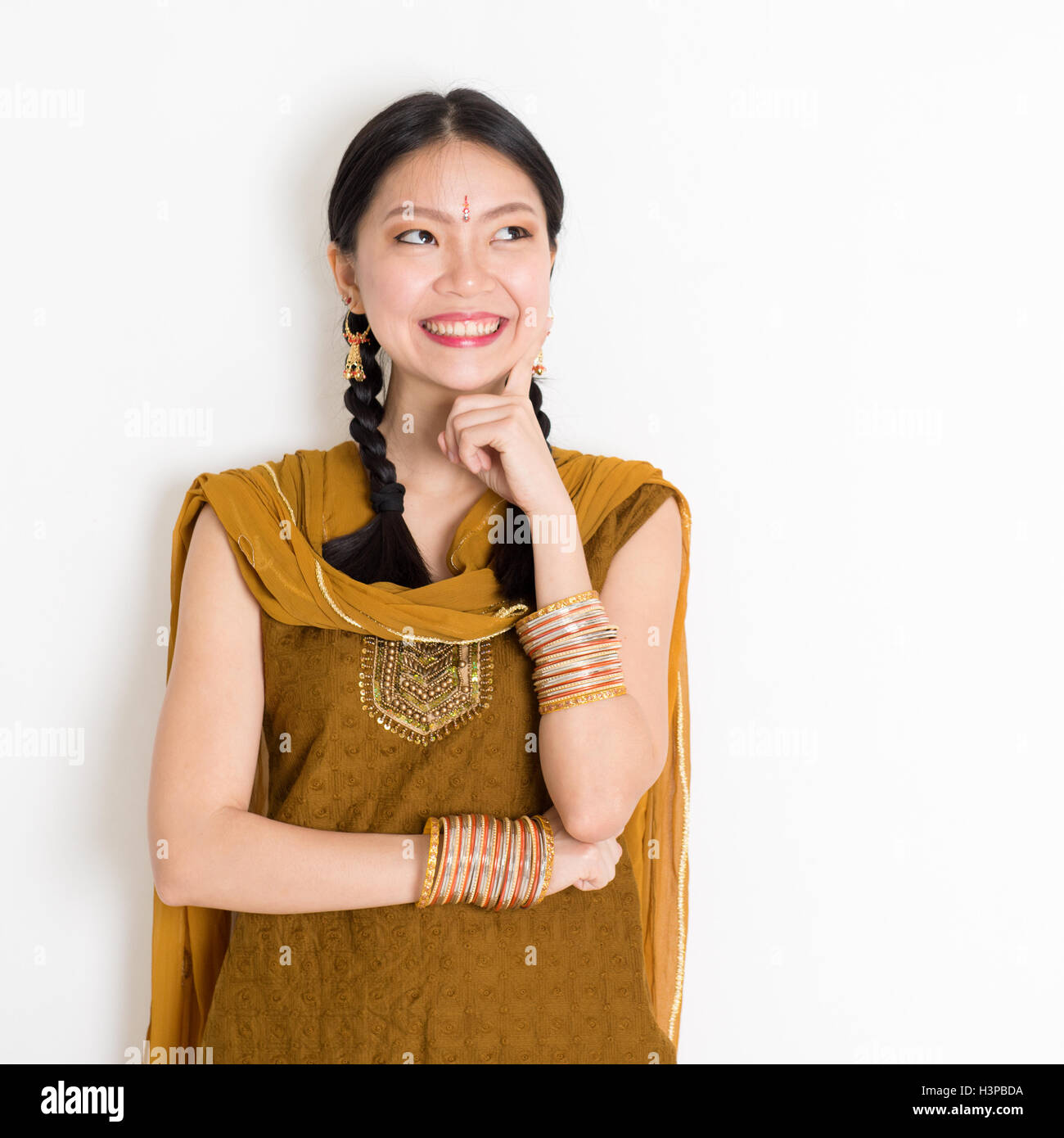 87067264c8 Portrait of thoughtful mixed race Indian Chinese girl in traditional  punjabi dress is thinking, standing on plain white backgrou