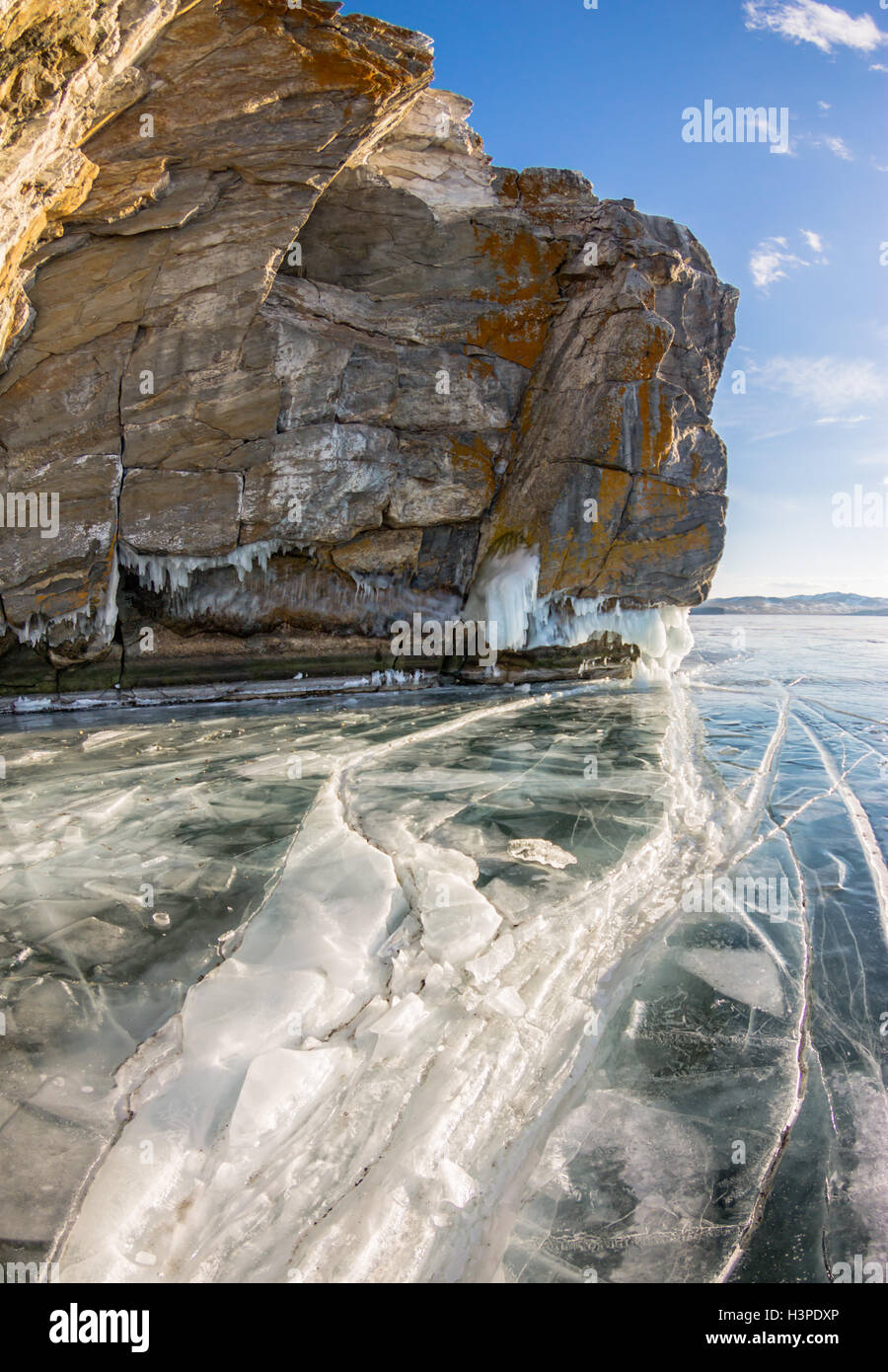 a crack in the ice and ice sokui on the rock. Olkhon Island. Lake Baikal - Stock Image