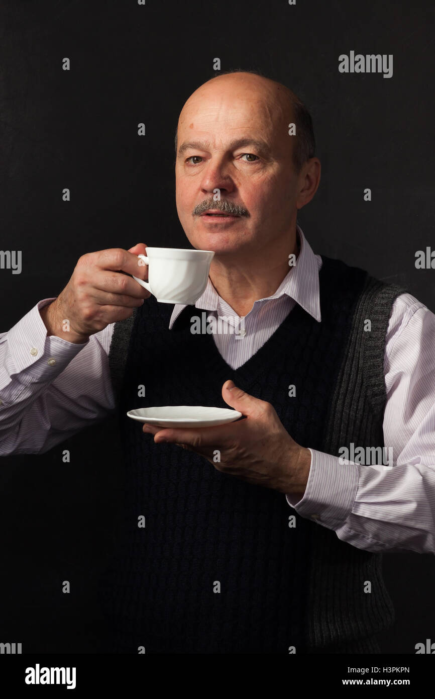 elderly bald man with a mustache takes a sip of coffee from a white mug. - Stock Image