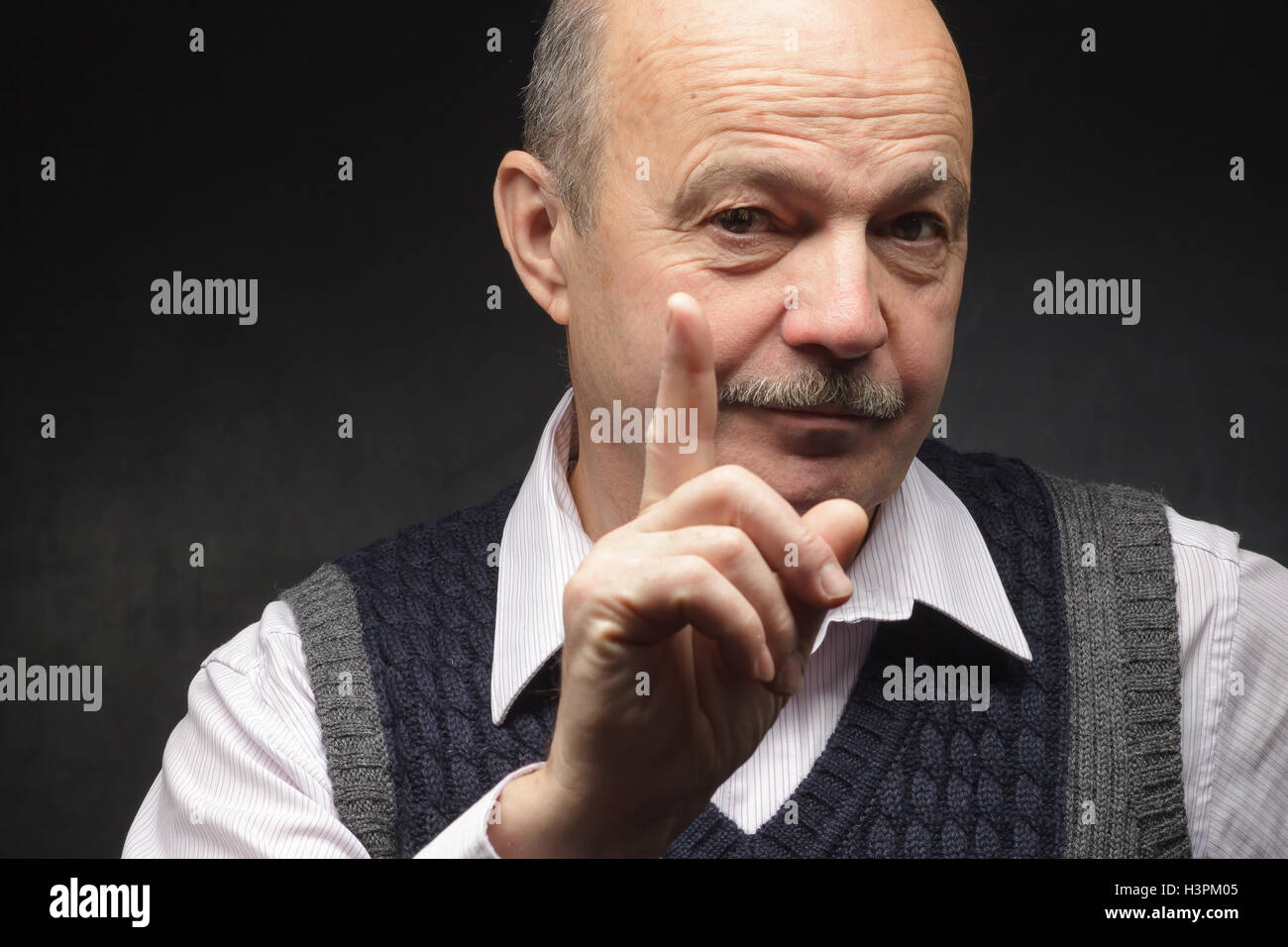 elderly man in a jacket and tie and looks strictly prohibits doing something - Stock Image