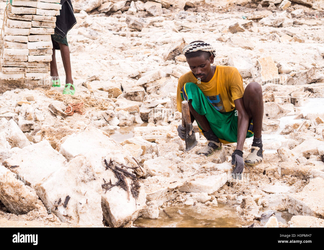 Afar man mining salt from salt flats in Afar region, Danakil Depression, Ethiopia. - Stock Image