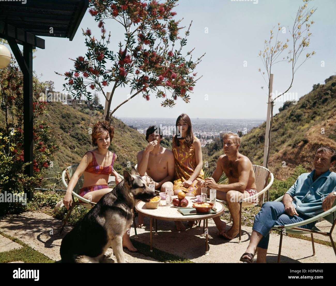 1960s THREE MEN TWO WOMEN WEARING BATHING SUITS SITTING ON PATIO WITH GERMAN SHEPHERD DOG LOS ANGELES HILLS CALIFORNIA - Stock Image