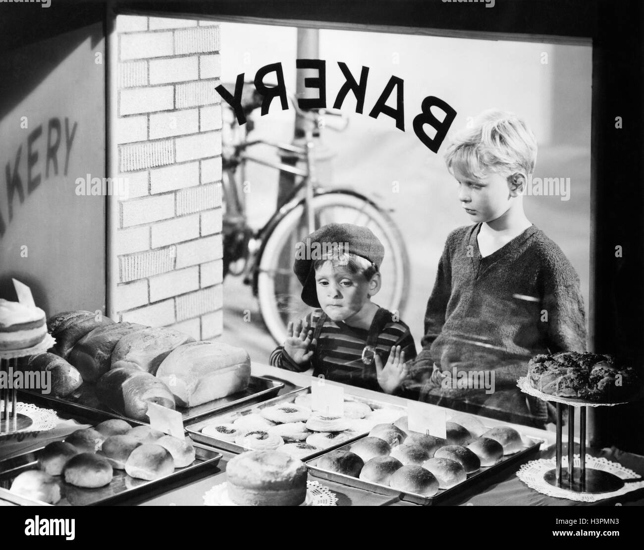1930s 1940s TWO BOYS LOOKING IN BAKERY SHOP WINDOW AT DESSERTS ONE BOY PRESSING HANDS AND NOSE AGAINST WINDOW Stock Photo