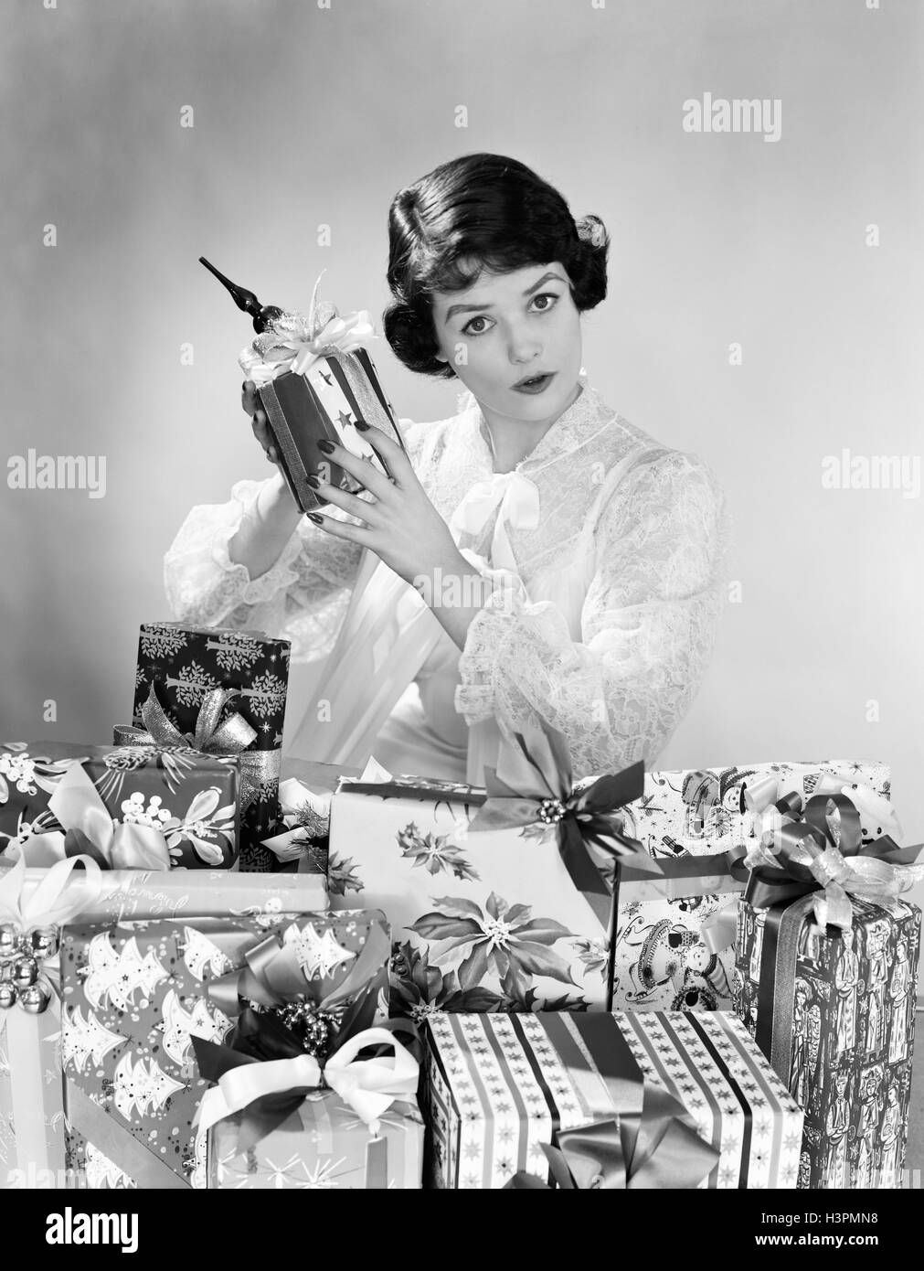 1950s WOMAN WEARING NIGHTGOWN CHRISTMAS MORNING SITTING BY PILE OF CHRISTMAS PRESENTS HOLDING SHAKING ONE PRESENT - Stock Image