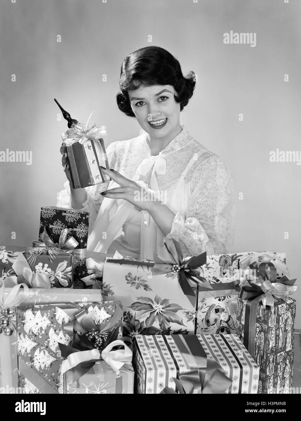 1950s SMILING WOMAN WEARING NIGHTGOWN CHRISTMAS MORNING SITTING BY PILE OF CHRISTMAS PRESENTS HOLDING ONE PRESENT - Stock Image