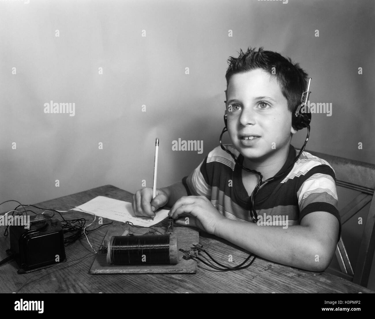 1930s 1940s 1950s YOUNG BOY WEARING HEADPHONES LISTENING TRANSCRIBING MORSE CODE FROM CRYSTAL RADIO - Stock Image