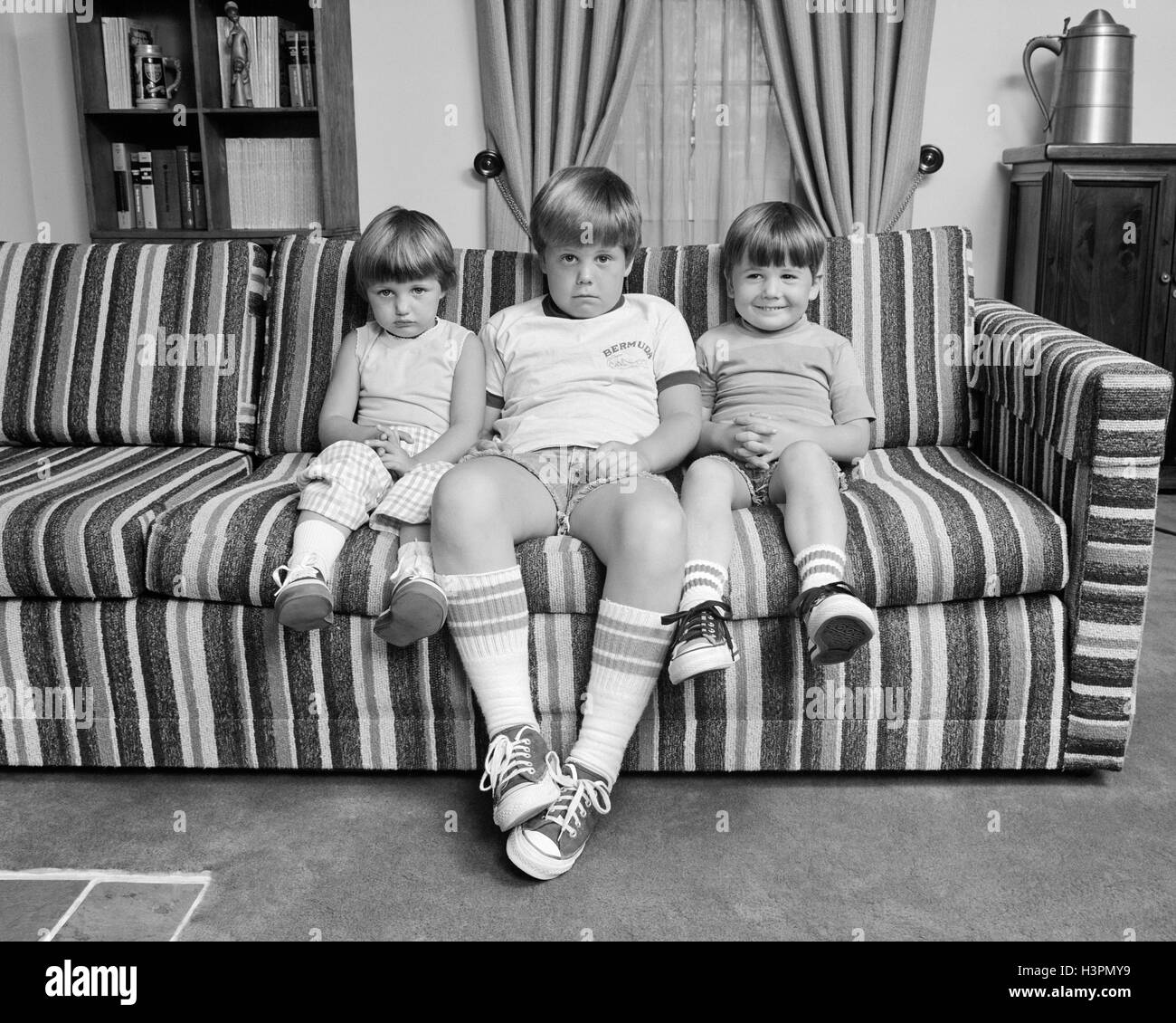 1970s THREE SIBLINGS SITTING ON COUCH LOOKING AT CAMERA - Stock Image