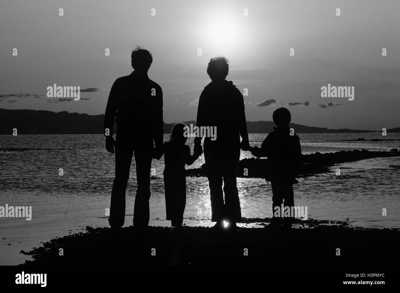 1980s REAR VIEW SILHOUETTE OF ANONYMOUS FAMILY OF FOUR STANDING ON BEACH HOLDING HANDS AT SUNSET - Stock Image