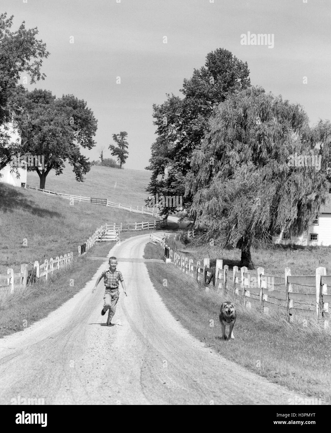 1950s BOY RUNNING DOWN COUNTRY LANE WITH HIS DOG - Stock Image