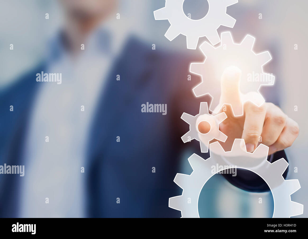 Business process automation and workflow improvement concept represented by a businessman touching a cogwheel and - Stock Image