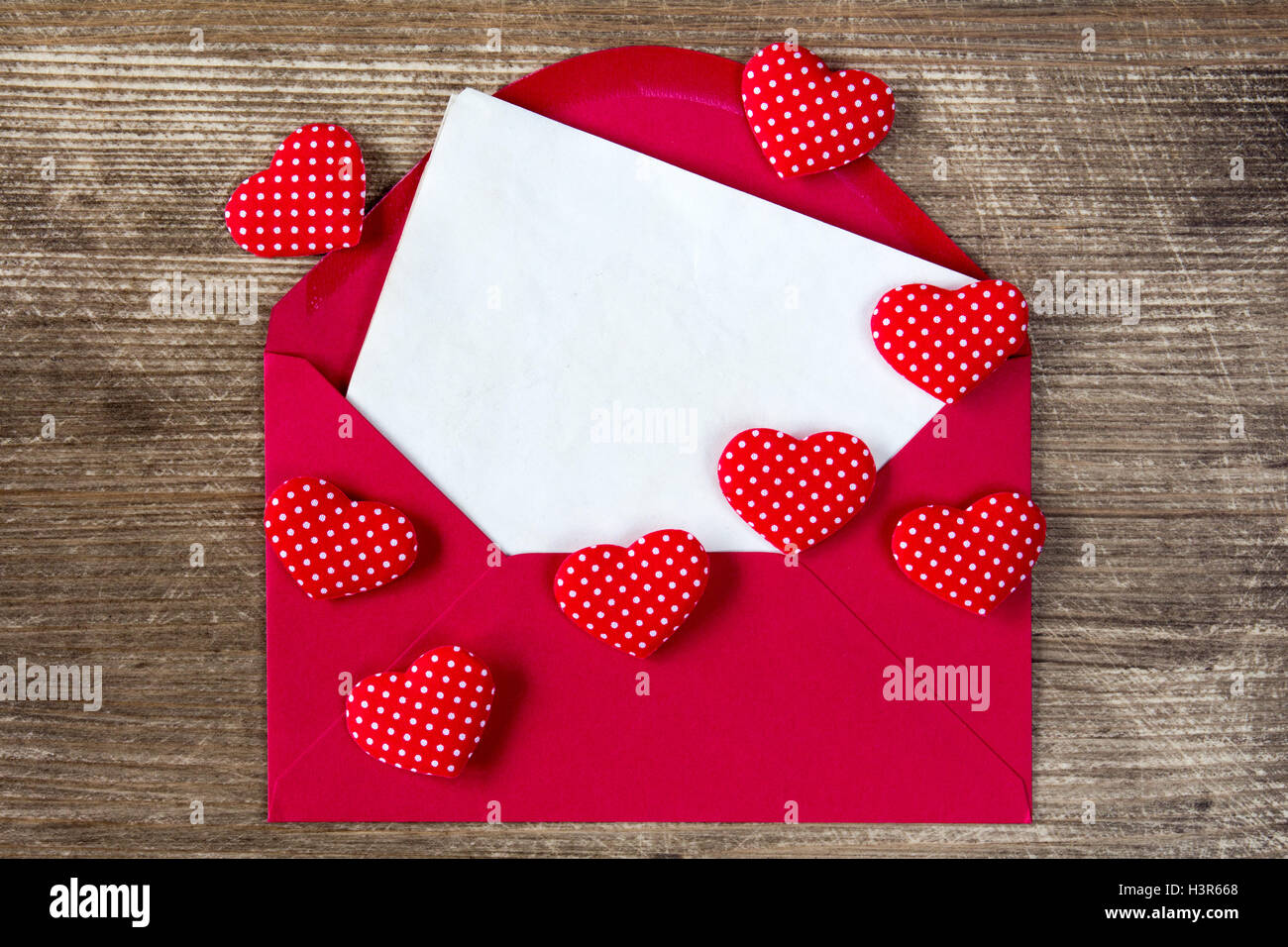 Open envelope with love letter and red hearts on the wooden