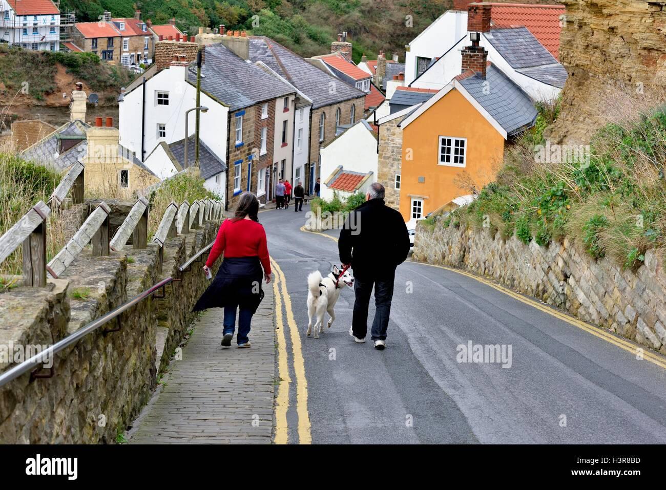 couple walking a dog. - Stock Image