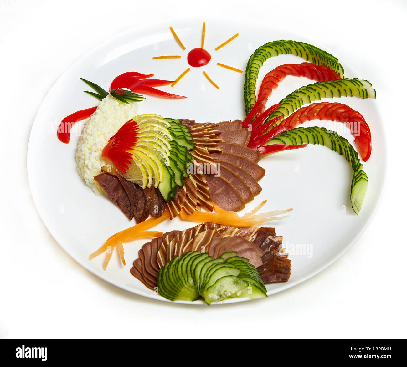 Big white plate with cold meat on a plate decorated like a rooster - a symbol of 2017 - Stock Image
