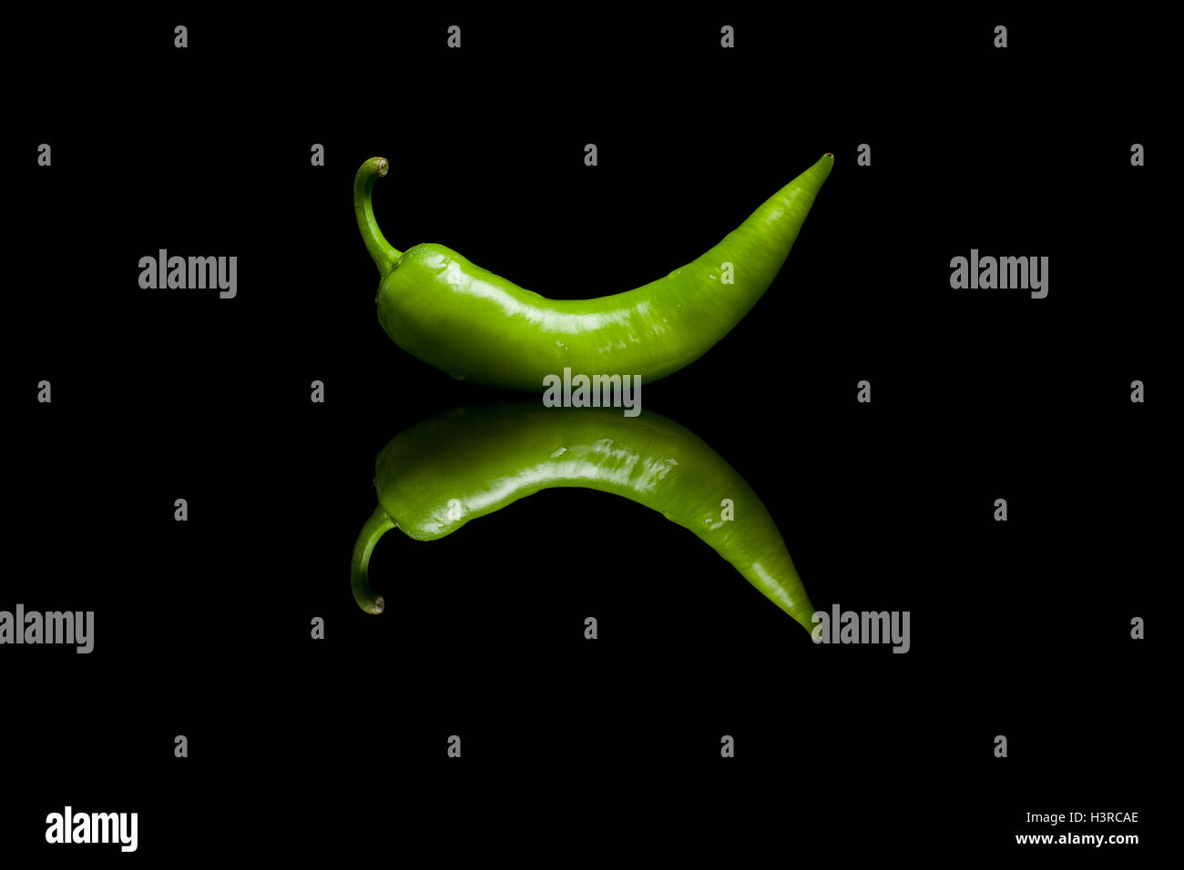 Green pepper isolated on black reflective background - Stock Image