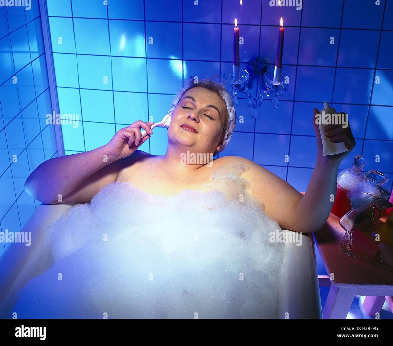 Bath, woman, overweight, facial massage, inside, bubble bath, bath, candles, thickly, overweight, massage, facial - Stock Image