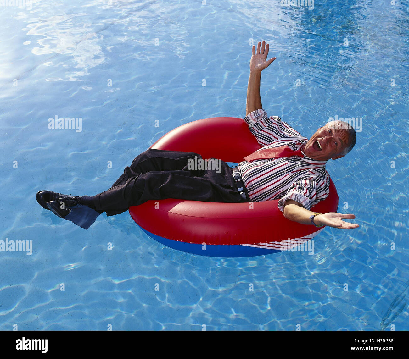 Swimming pool, man, swimming tyre, laugh, gesture, carefree, pool, water, businessman, dresses, allow to lie, do - Stock Image