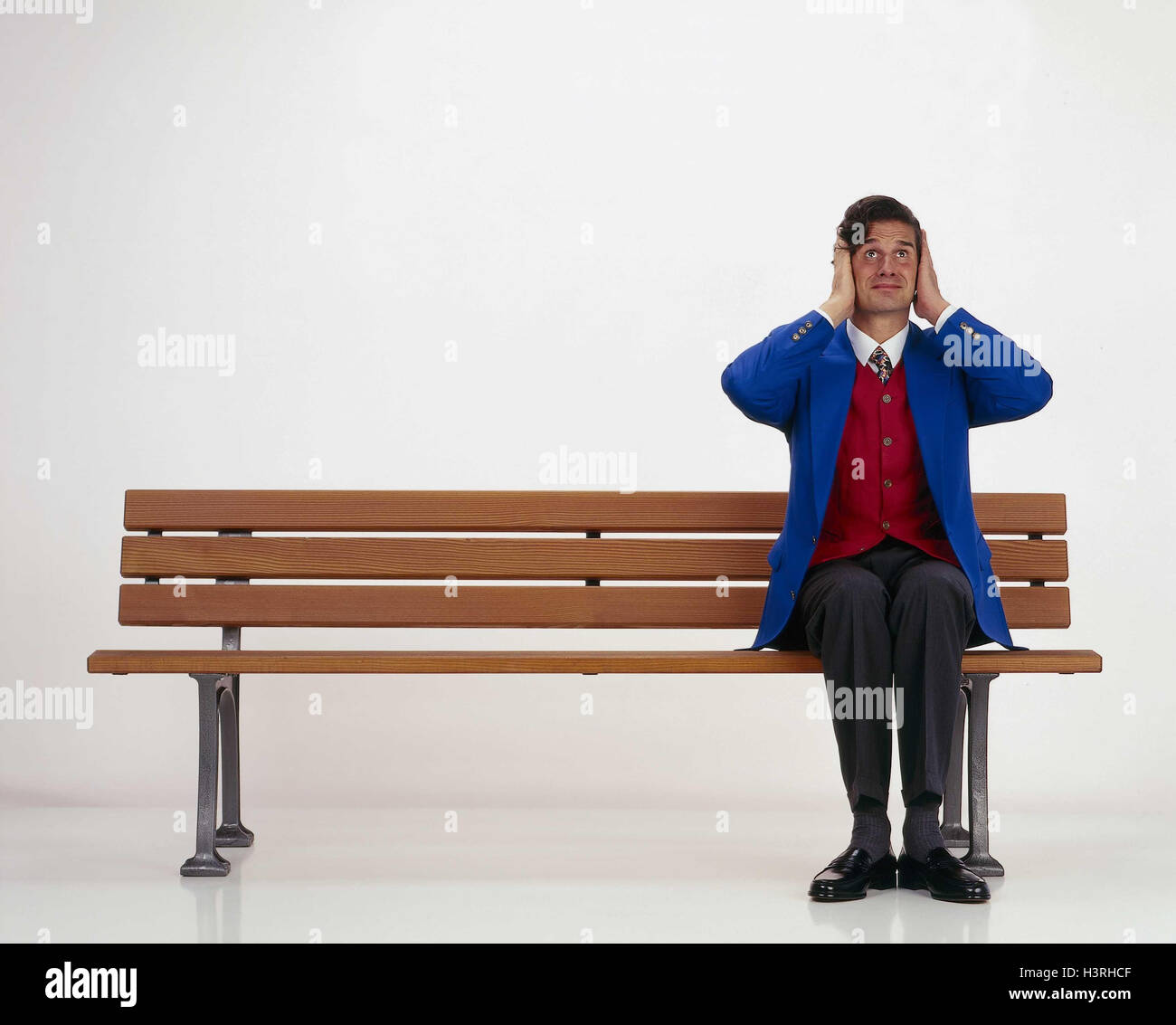 Man, bank, sit, keep closed gesture, ears inside, studio, park-bench, noise, loudly, stress, stressed, overallocated, - Stock Image