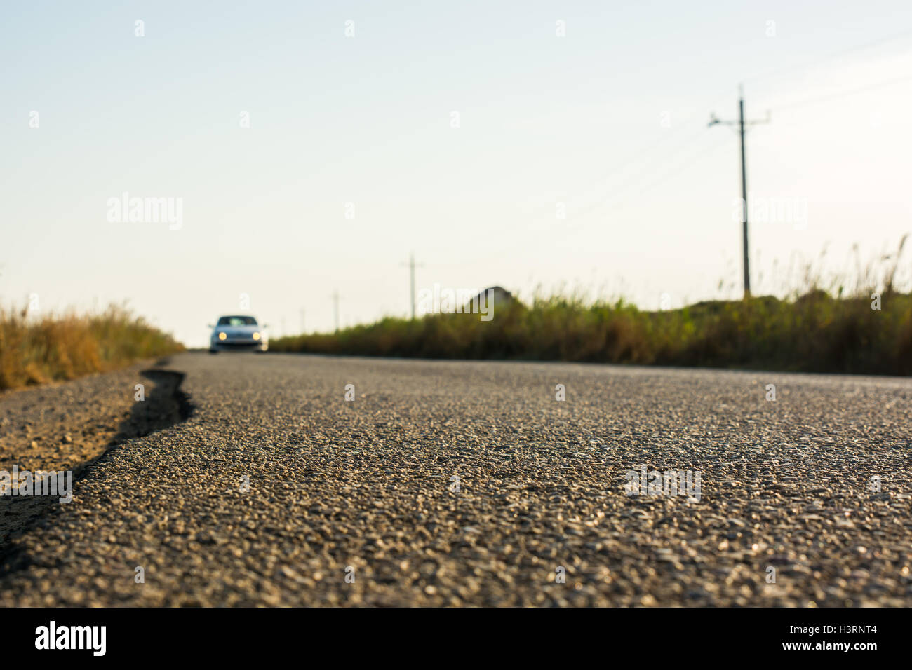 Detail of the asphalt of a country road while a car aproaches. - Stock Image
