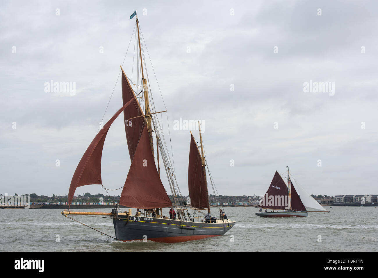 Sailing smack CK18 Pioneer tacking off Mersea Stone in the Colne estuary at the start of a race. - Stock Image