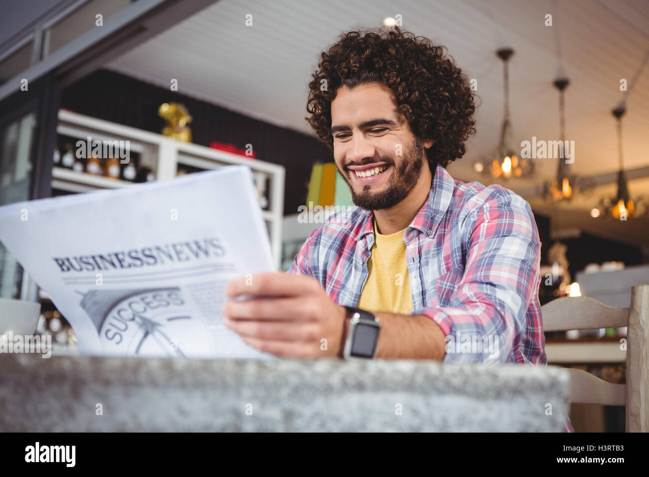 Man smiling while reading newspaper - Stock Image