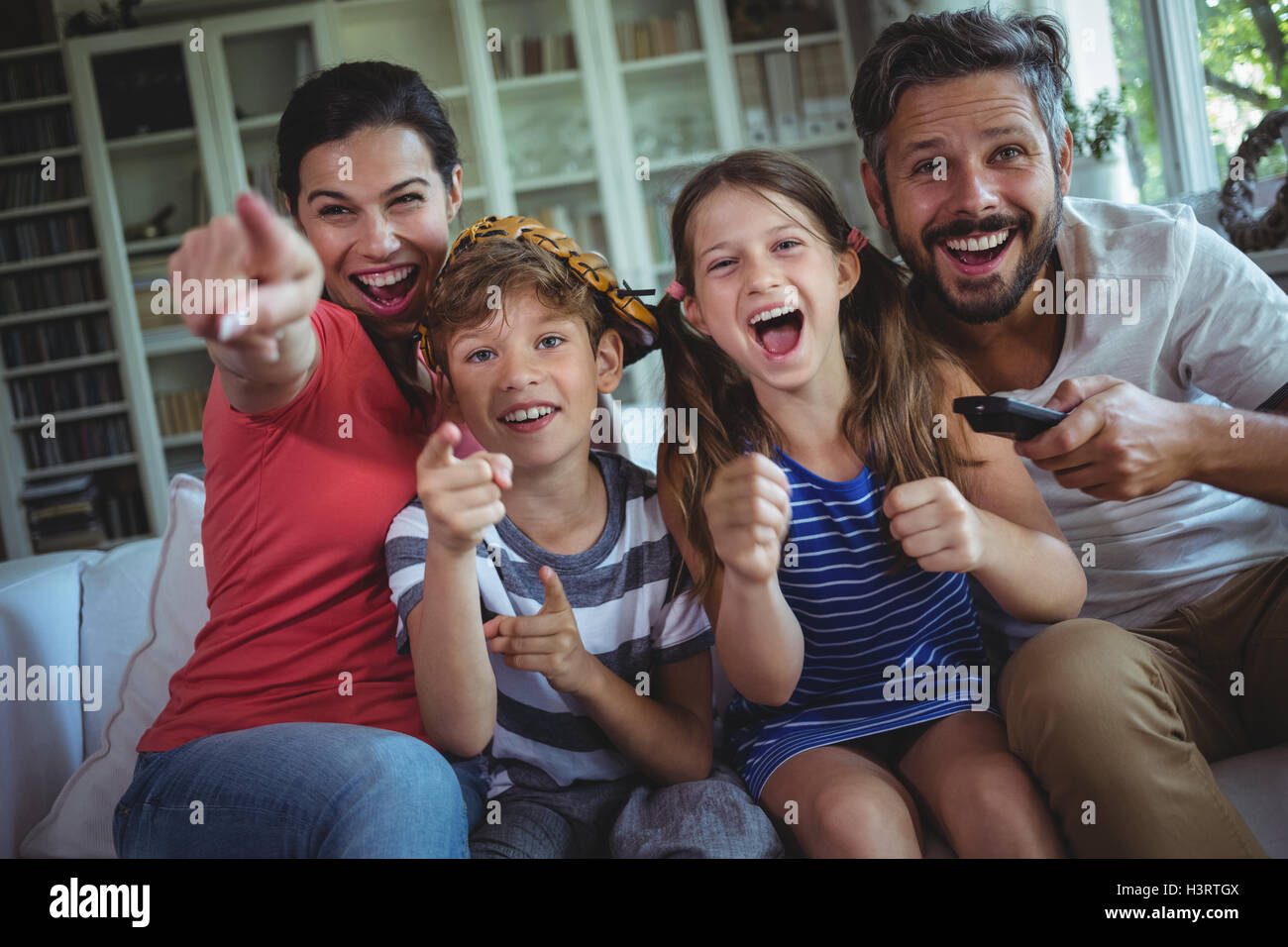 Excited family watching television - Stock Image