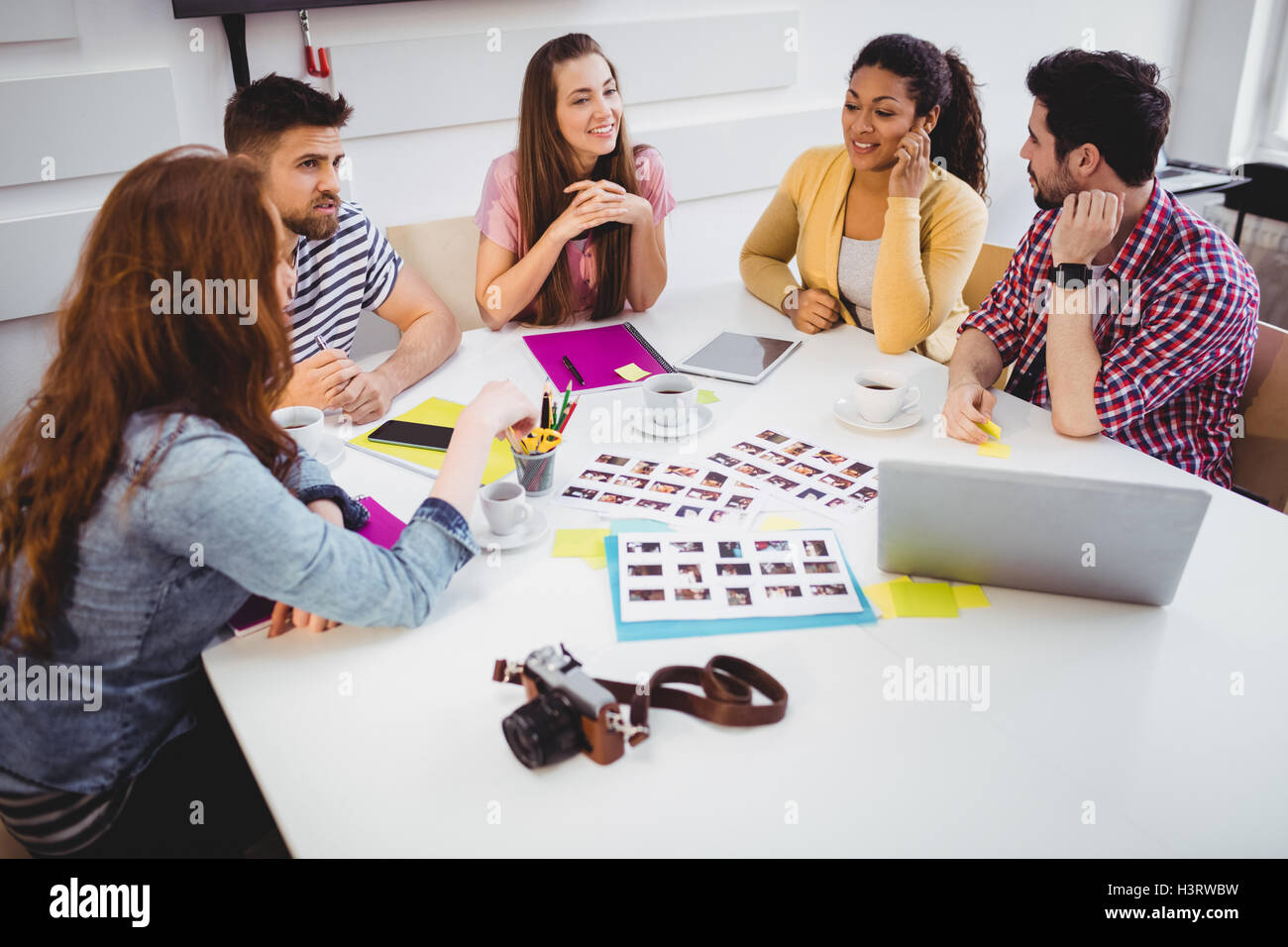 Editors discussing photographs in meeting at creative office - Stock Image