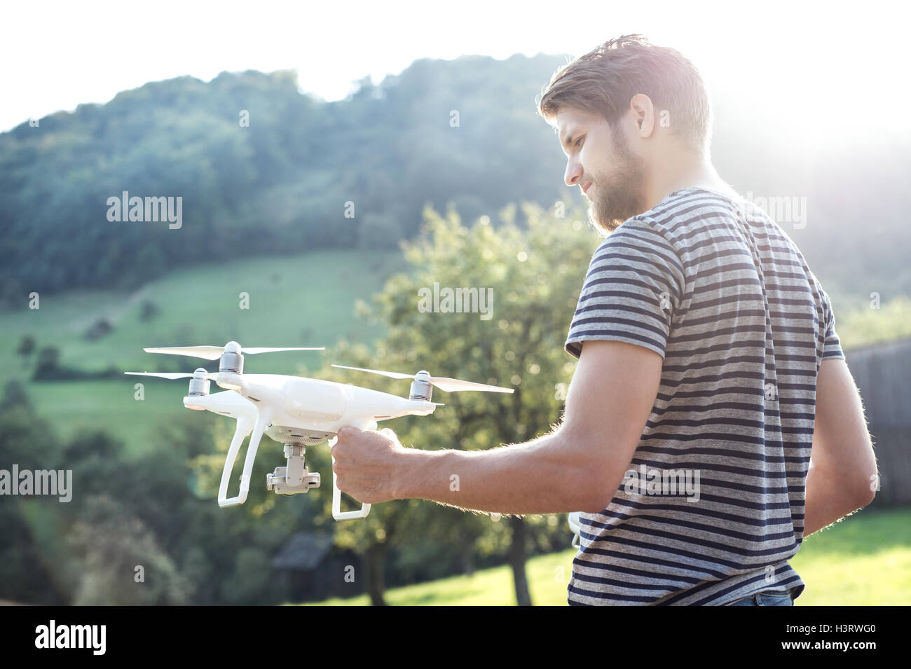 Young hipster man holding drone. Sunny green nature. - Stock Image