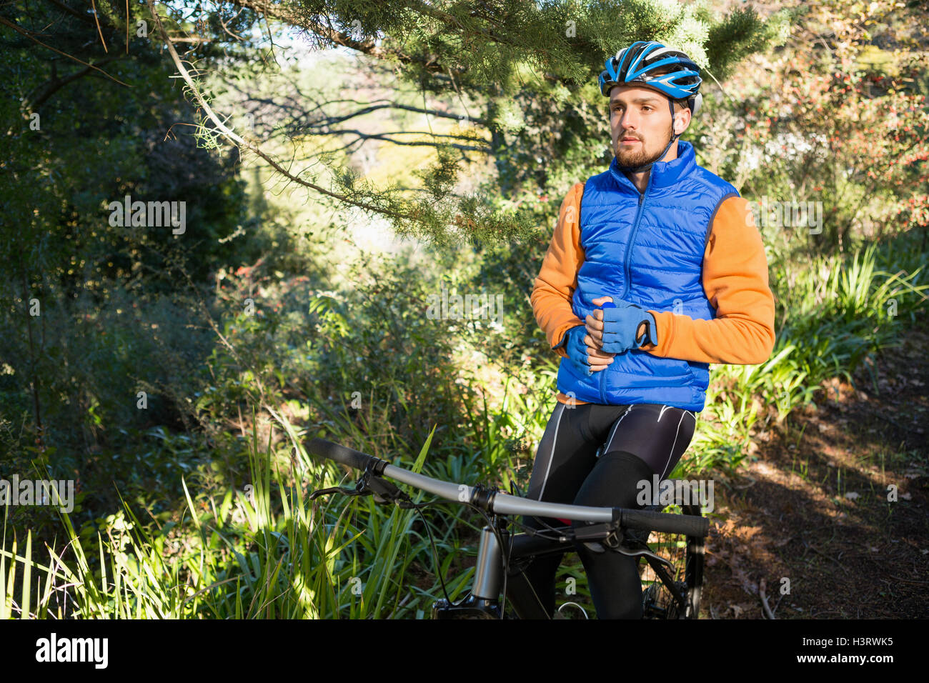 Male mountain holding water bottle standing with bicycle - Stock Image