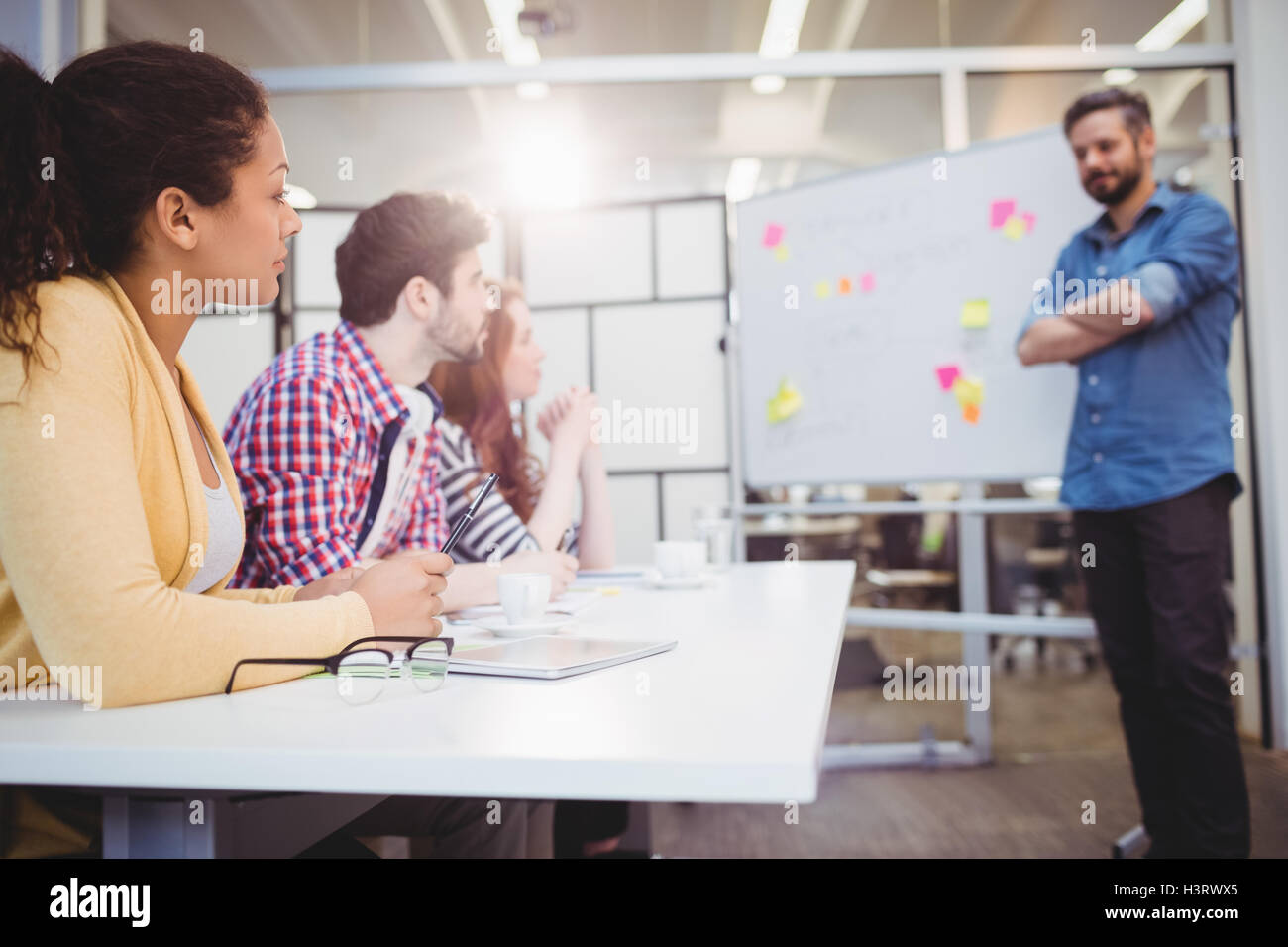 Executive standing in front of colleagues in meeting room at creative office - Stock Image