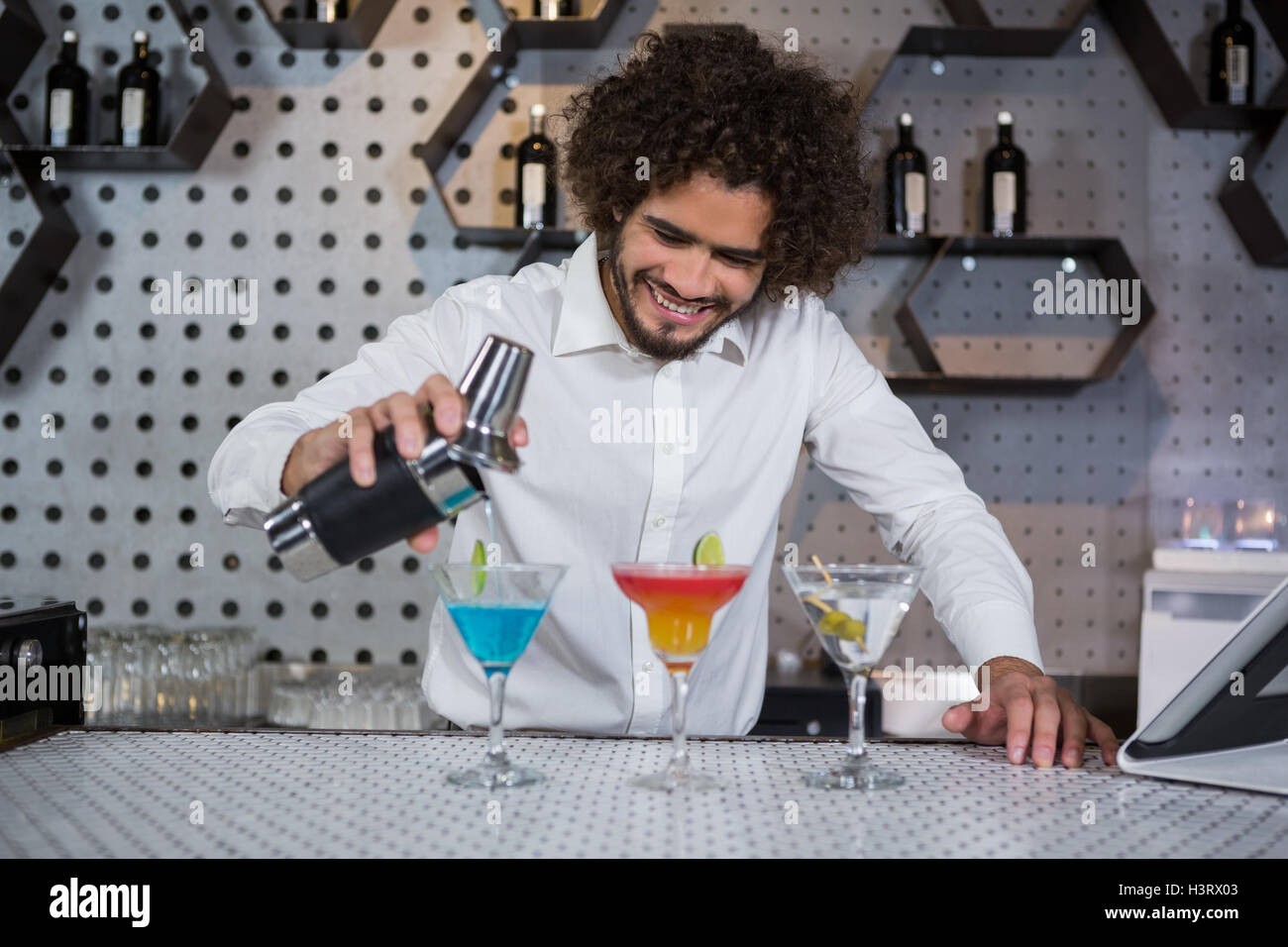 Bartender pouring cocktail into glasses - Stock Image