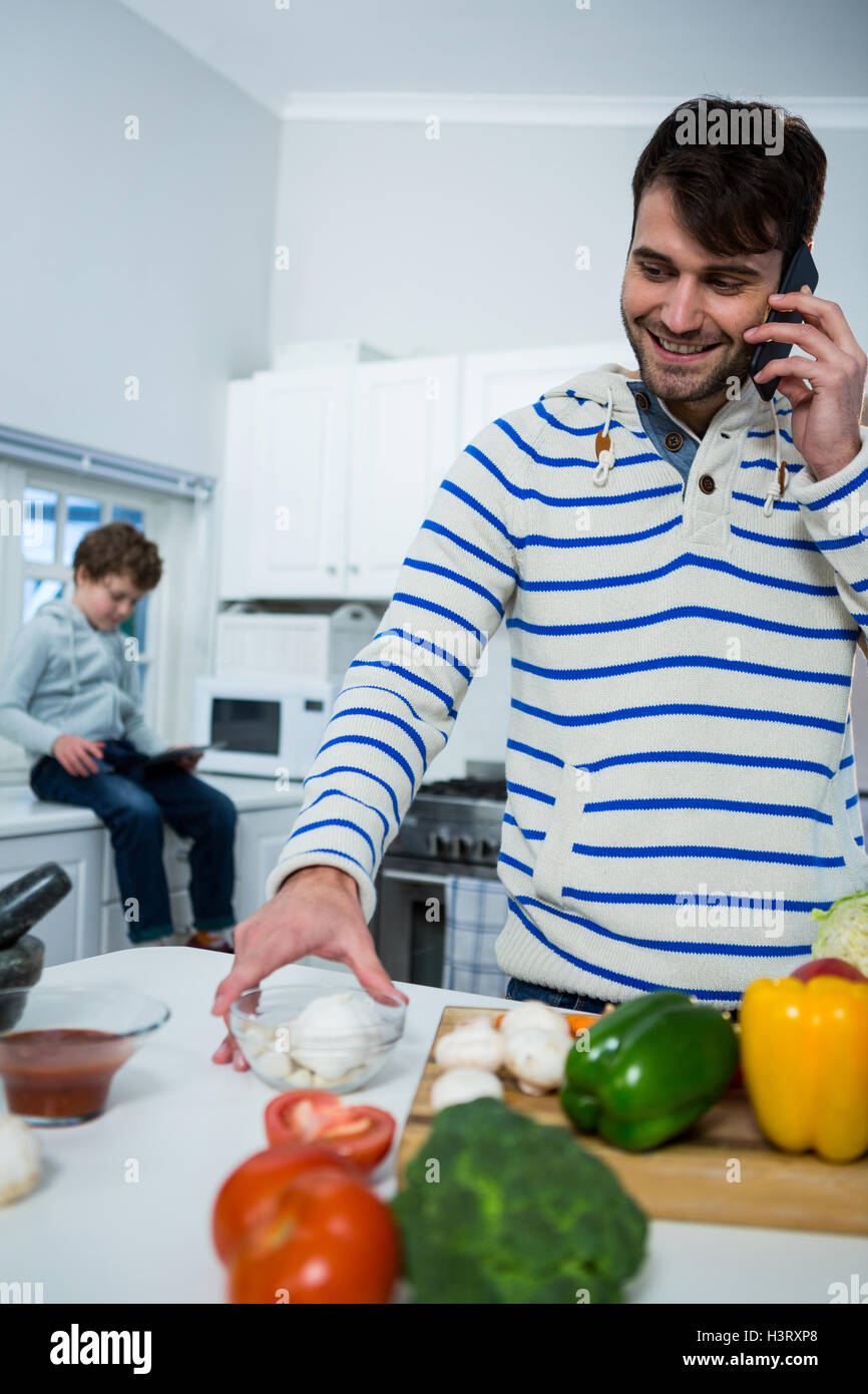 Father talking on mobile phone while working in the kitchen Stock ...