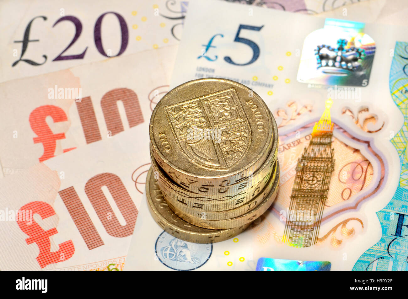 British money - pound coins on notes, including new (2016) polymer £5 - Stock Image