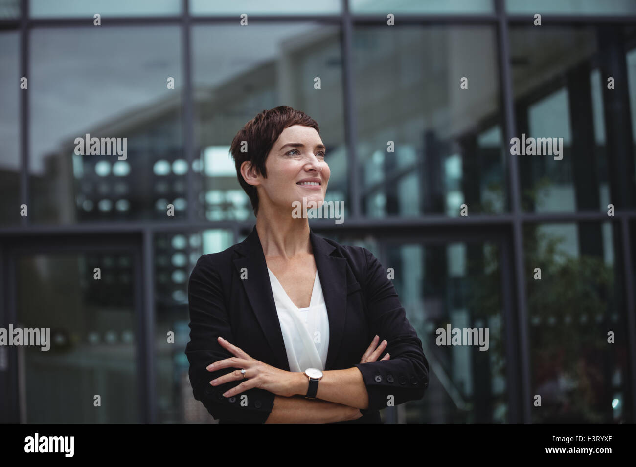 Smiling businesswoman standing in office premises Stock Photo
