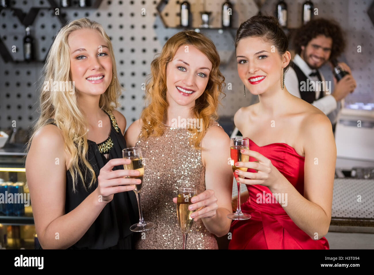 Three smiling friend having glass of champagne - Stock Image