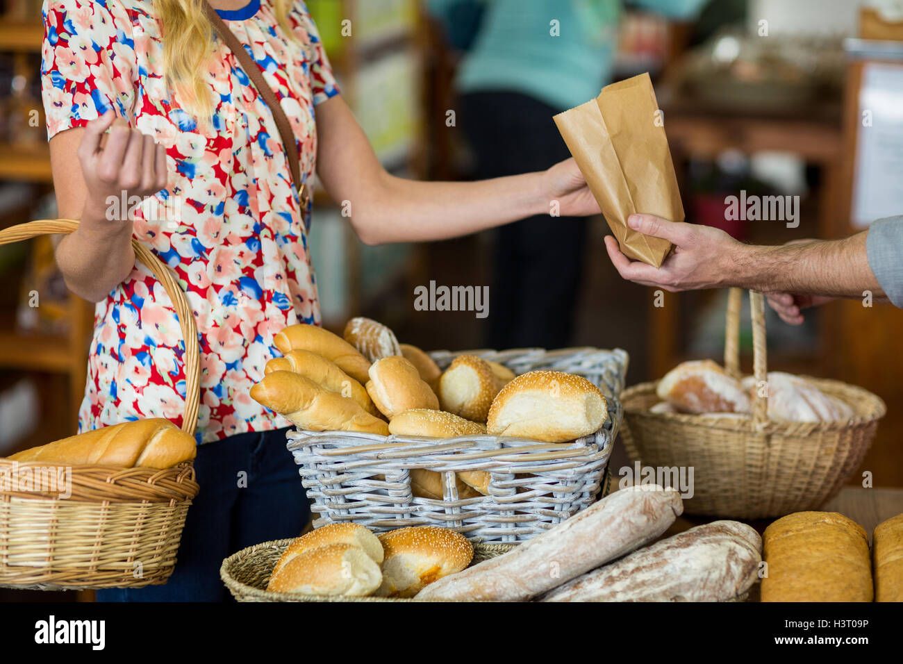 Mid section of woman purchasing bread - Stock Image