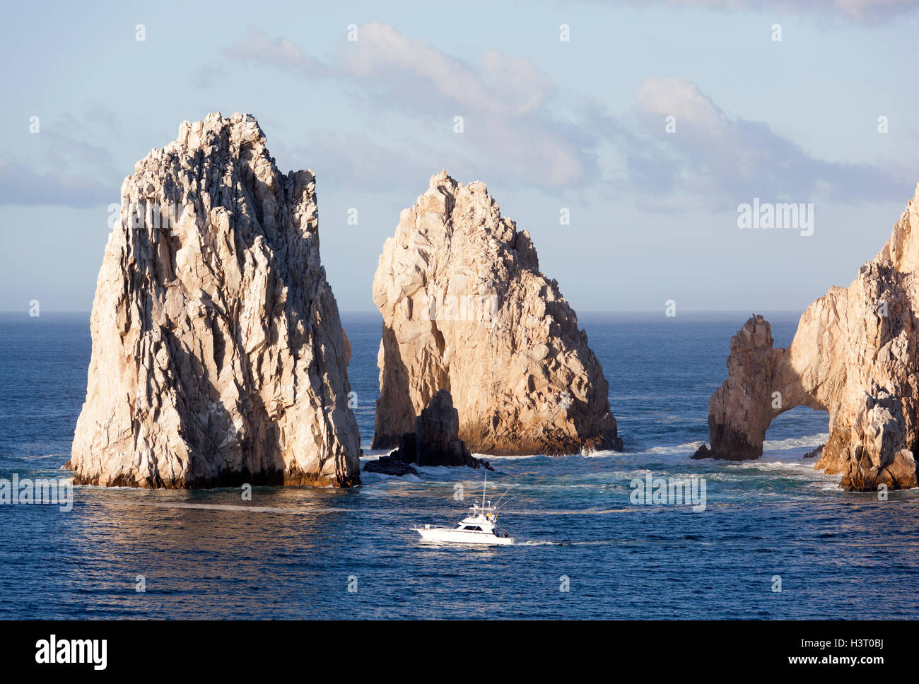 The boat passing by famous rocks of Cabo San Lucas resort town (Mexico). - Stock Image