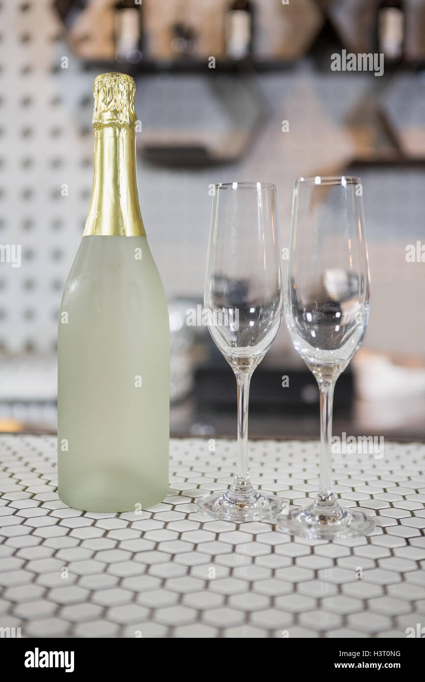 Champagne bottle and champagne flute on bar counter - Stock Image