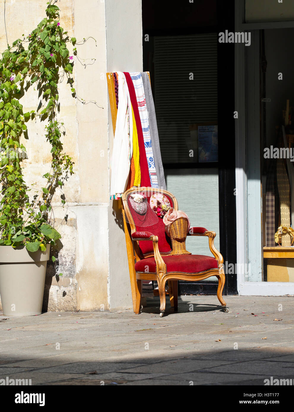 Armchair with hats on a sidewalk - Stock Image